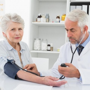 doctor-taking-blood-pressure-of-his-retired-patient